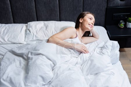 cheerful woman looking away and lying on bed