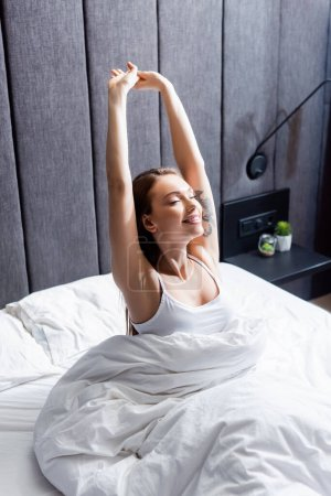 Photo for Beautiful woman with closed eyes stretching in bed - Royalty Free Image