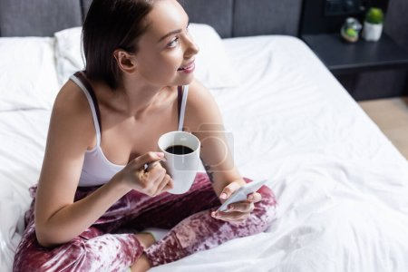 happy young woman holding smartphone and cup of coffee in bed