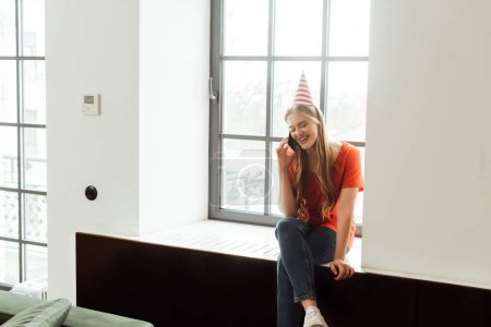 Photo for Smiling girl in party cap sitting on window sill and talking on smartphone - Royalty Free Image