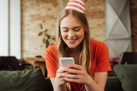 Photo for Cheerful young woman in party cap using smartphone - Royalty Free Image