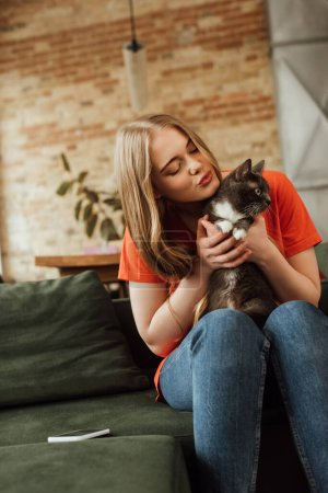 Photo pour Attrayant jeune femme tenant dans les bras chat mignon près smartphone sur canapé - image libre de droit