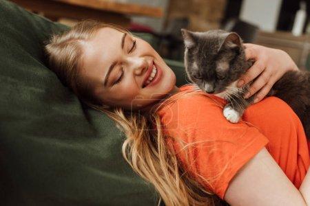 Photo pour Joyeuse jeune femme regardant chat mignon dans le salon - image libre de droit