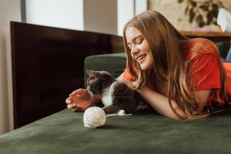 Photo for Cheerful girl playing cute cat near ball of yarn on sofa - Royalty Free Image