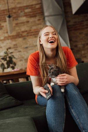 Photo pour Fille heureuse tenant télécommande et riant près de chat mignon - image libre de droit