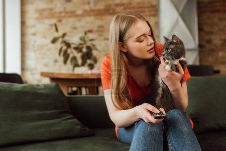 Photo pour Jeune femme tenant télécommande et regardant chat mignon - image libre de droit