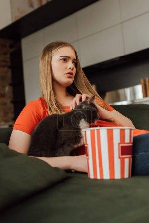 Junge Frau berührt Katze beim Ansehen von Film in der Nähe von Popcorn-Eimer