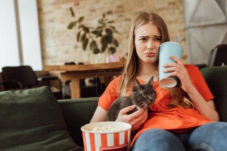Photo pour Foyer sélectif de femme triste tenant tasse jetable avec soda près seau de maïs soufflé et chat tout en regardant le film dans le salon - image libre de droit