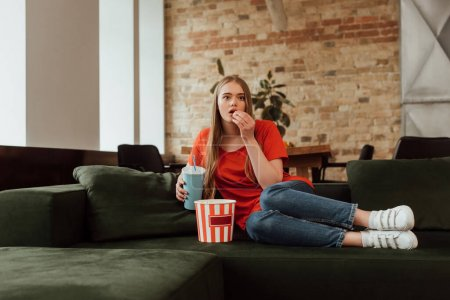 attractive girl eating popcorn, holding disposable cup and watching movie in living room