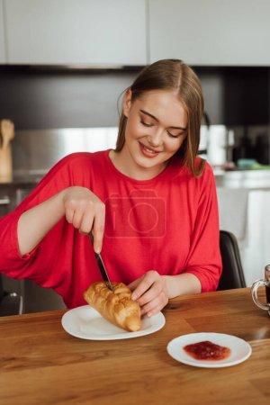 glückliches Mädchen hält Messer in der Hand und schneidet leckeres Croissant auf Teller