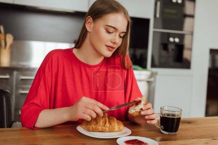 attraktives Mädchen hält Messer mit süßer Marmelade in der Nähe von leckerem Croissant
