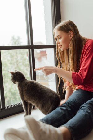selective focus of young woman pointing with finger at window near cute cat