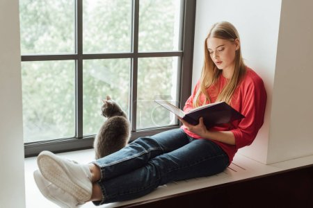 Photo for Beautiful girl sitting on window sill and reading book near cute cat - Royalty Free Image