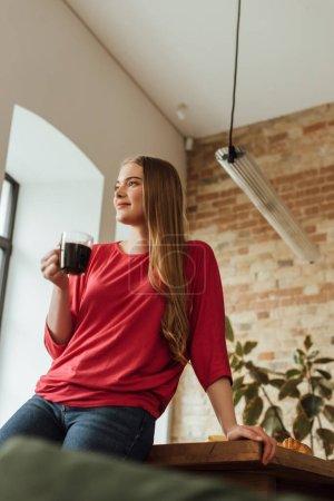 enfoque selectivo de la mujer alegre sosteniendo la taza de café y mirando hacia otro lado