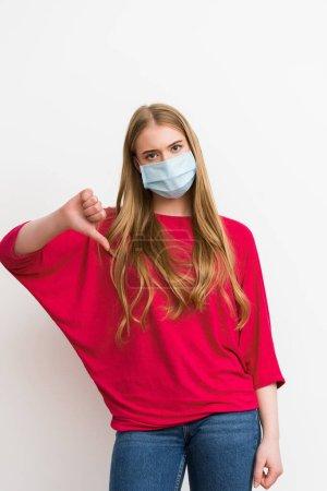Photo pour Jeune femme en masque médical montrant pouce vers le bas isolé sur blanc - image libre de droit