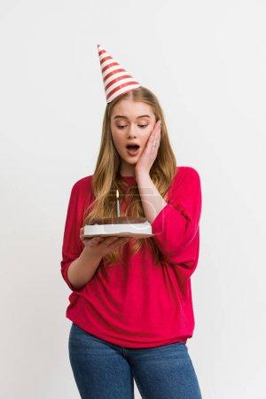 Photo pour Surprise fille en casquette de fête regardant le gâteau d'anniversaire isolé sur blanc - image libre de droit