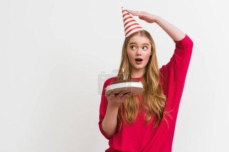Photo pour Surprise fille touchant la casquette de fête et tenant le gâteau d'anniversaire isolé sur blanc - image libre de droit