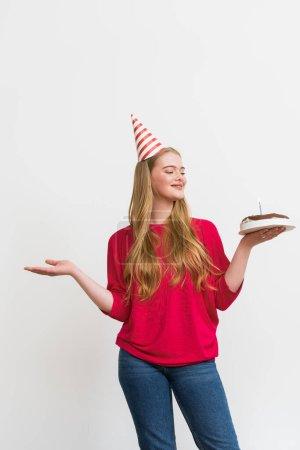 Photo pour Jeune femme en chapeau de fête tenant gâteau d'anniversaire et geste isolé sur blanc - image libre de droit