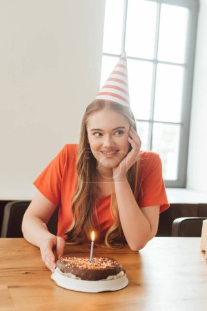 Photo pour Femme joyeuse en chapeau de fête regardant loin près d'un délicieux gâteau d'anniversaire - image libre de droit