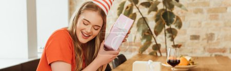 Photo for Panoramic crop of cheerful girl holding present near glass of red wine - Royalty Free Image