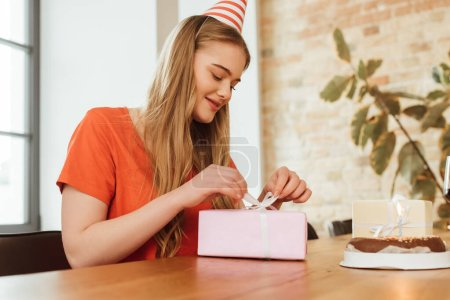 Photo for Cheerful girl touching ribbon on present near birthday cake - Royalty Free Image