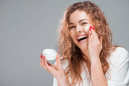 Photo for Cheerful young woman applying face cream isolated on grey - Royalty Free Image