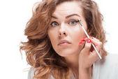 woman putting eyeliner