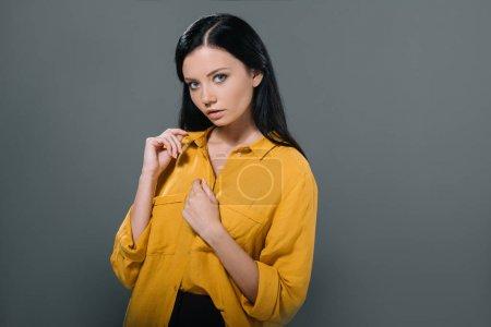 Photo pour Femme brune séduisante posant en chemisier jaune, isolée sur gris - image libre de droit