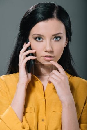 brunette woman talking on smartphone