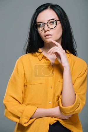 Photo pour Élégante femme sensuelle posant en chemisier jaune et des lunettes élégantes, isolé sur gris - image libre de droit
