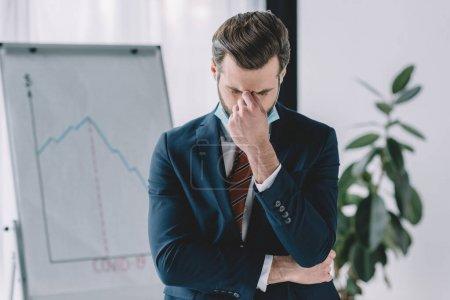 depressiver Geschäftsmann mit gesenktem Kopf und geschlossenen Augen in der Nähe von Flipchart mit Grafiken, die Rezession zeigen