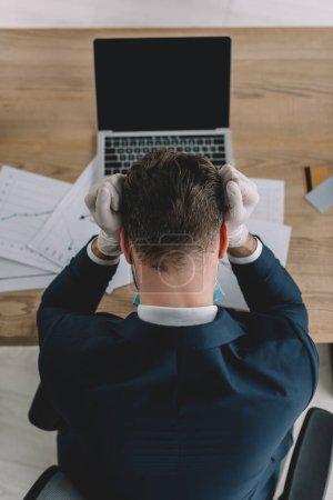 Ansicht von oben: gestresster Geschäftsmann in Latexhandschuhen am Arbeitsplatz neben Laptop und Dokumenten mit gesenktem Kopf