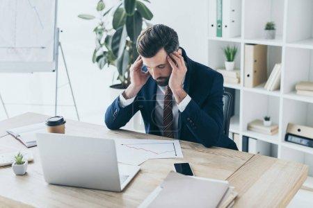 depressiver Geschäftsmann mit gesenktem Kopf am Arbeitsplatz sitzend mit geschlossenen Augen