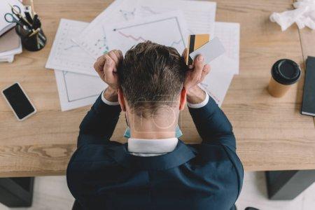 Draufsicht eines depressiven Geschäftsmannes, der Kreditkarten hält, während er mit gesenktem Kopf am Arbeitsplatz in der Nähe von Dokumenten sitzt