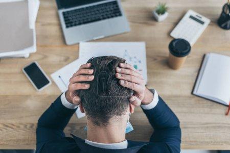 Draufsicht eines depressiven Geschäftsmannes, der den Kopf mit Händen bedeckt, während er am Arbeitsplatz in der Nähe von Geräten und Dokumenten sitzt