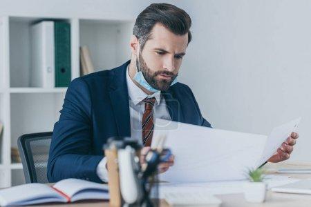 Photo pour Attention sélective od sérieux, homme d'affaires réfléchi regardant des documents tout en étant assis sur le lieu de travail - image libre de droit