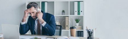panoramic shot of upset businessman touching forehead while talking on smartphone at workplace