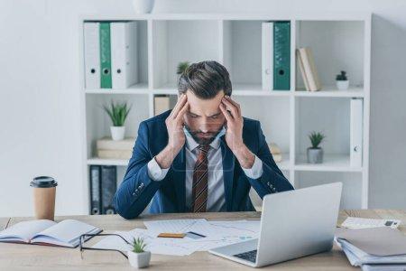 homme d'affaires déprimé touchant la tête inclinée tout en étant assis les yeux fermés sur le lieu de travail