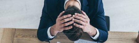 plano panorámico de empresario deprimido cogido de la mano en la cabeza inclinada mientras se sienta en el escritorio en la oficina