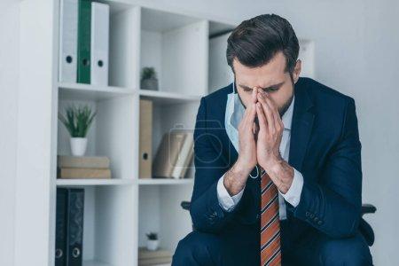 Photo pour Homme d'affaires déprimé touchant le visage alors qu'il était assis au bureau avec la tête inclinée et les yeux fermés - image libre de droit