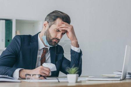 selektiv fokussiert auf erschöpfte, aufgebrachte Geschäftsleute, die zerknülltes Papier in der Hand halten, während sie unter Kopfschmerzen mit geschlossenen Augen leiden