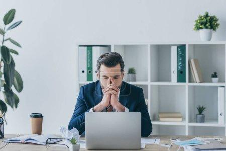 depressiver Geschäftsmann hält die Hände vor dem Gesicht, während er mit geschlossenen Augen am Arbeitsplatz sitzt