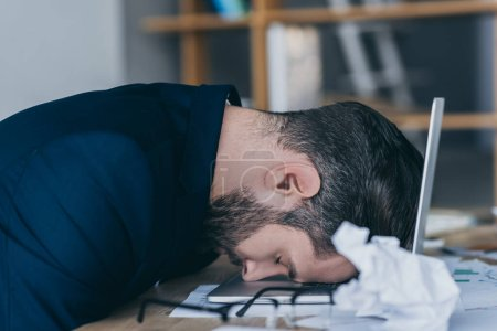 depressed businessman with closed eyes sitting at workplace with head on laptop near crumpled paper