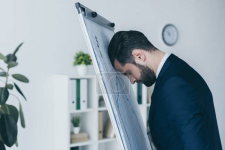 Photo for Depressed businessman standing with closed eyes and leaning at flipchart with forehead - Royalty Free Image