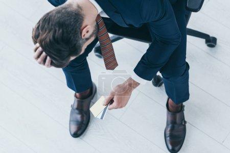 Blick über den Kopf eines aufgebrachten Geschäftsmannes, der mit gesenktem Kopf auf einem Bürostuhl sitzt und Kreditkarten hält