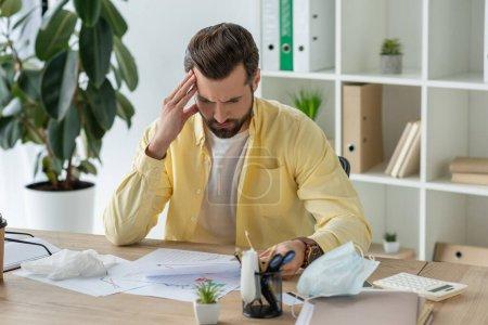 nachdenklicher Geschäftsmann, der am Arbeitsplatz sitzt und sich Dokumente ansieht