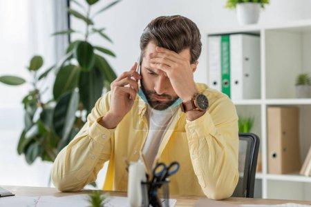 Selektiver Fokus eines depressiven Geschäftsmannes, der im Büro mit dem Smartphone an der Stirn spricht