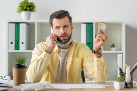 Selektiver Fokus besorgter Geschäftsleute, die mit dem Smartphone sprechen, während sie Kreditkarten halten