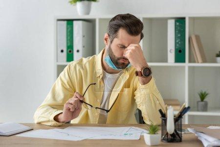 Erschöpfter Geschäftsmann mit Brille und anrührendem Gesicht am Arbeitsplatz in der Nähe von Dokumenten