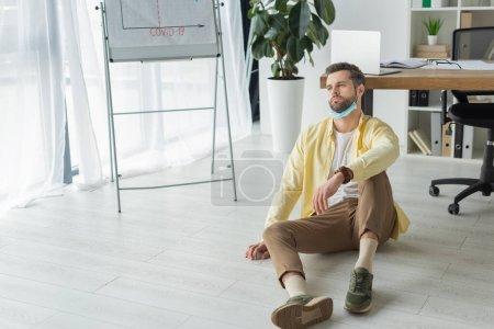 Photo pour Homme d'affaires déprimé assis sur le sol près de tableau à feuilles avec inscription covid-19 et détournant les yeux - image libre de droit